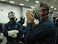US Navy 060116-N-3455P-002 Aviation Structural Mechanic 1st Class Steve L. Flemens demonstrates how to check for a proper seal of an MCU-2P gas mask.jpg