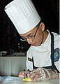 US Navy 060509-N-3560G-010 Culinary Specialist 3rd Class Guangfeng Zhou assigned to Naval Mobile Construction Battalion Four (NMCB-4) prepares ingredients to be used in a competition dinner.jpg