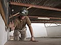 US Navy 060614-N-0411D-103 U.S. Navy Utilitiesman 2nd Class Richard Cruikshank, assigned to Naval Mobile Construction Battalion Seven (NMCB-7), hammers the last section of ceiling plywood.jpg