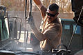 US Navy 070131-N-1625W-008 Construction Mechanic 2nd Class Brian Seaverns of Tacoma, Wash., power washes a vehicle engine before doing maintenance at the Construction Mechanic Shop in Camp Fallujah, Iraq.jpg