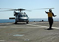 US Navy 070920-N-5120C-146 Aviation Electronics Technician 3rd Class Lawrence R. Callier signals to the aircrew of a MH-60S Seahawk preparing for takeoff from amphibious command ship USS Mount Whitney (LCC 20).jpg