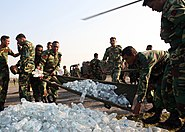 US Navy 071123-M-7696M-099 Bangladeshi soldiers use a stretcher to unload a shipment of bottled water delivered by Marines of Marine Medium Helicopter Squadron (HMM) 261