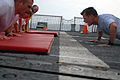 US Navy 080805-N-4995K-450 Command Master Chief Christopher Angstead performs push-ups with new chief petty officer selectees.jpg