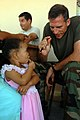 US Navy 081007-N-3595W-078 Lt. Cmdr. Nathan Uebelhoer, a dermatologist embarked aboard the amphibious assault ship USS Kearsarge (LHD 3), talks with a little girl at a local medical clinic during a community service project in.jpg