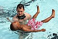US Navy 090608-N-8110K-035 Navy Diver 2nd Class Bobby Demay, assigned to Mobile Diving and Salvage Unit 2 based at Navy Amphibious Base Little Creek, Va., teaches a child how to float.jpg