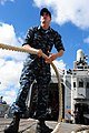 US Navy 100706-N-7200S-017 Fire Controlman 2nd Class Kevin Walters hauls in a mooring line during sea and anchor detail aboard the guided-missile frigate USS McClusky (FFG 41) while getting underway for Rim of the Pacific (RIMP.jpg