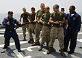 US Navy 100707-N-3154P-037 Aviation Boatswain's Mate 1st Class Jesse Seagrave and Aviation Boatswain's Mate Victor Perry teach Marines the proper way to handle a hose during an aviation fire drill.jpg