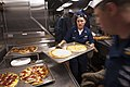 US Navy 100717-N-5319A-028 Hospital Corpsman 1st Class Erin Brooks prepares pizzas as the Navy and Marine Corps E-6 community aboard USS New Orleans (LPD 18) take over galley duties for dinner.jpg