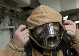 US Navy 120109-N-DR144-096 Machinist's Mate 2nd Class Janice Torres dons a firefighting ensemble.jpg