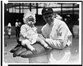 Walter Johnson, half-length portrait, facing slightly left, holding little girl on large glove LCCN93510964.jpg