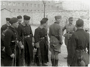 Trawniki concentration camp - Trawniki shooters during the Warsaw Ghetto Uprising, with Jürgen Stroop (on the right), 1943. Note: their military coats come from the German Allgemeine-SS surplus no longer used by the SS