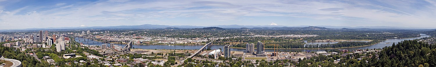 A panorama of Portland, with many buildings on either side of the Willamette River, with a number of bridges crossing it