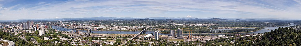 The Willamette River runs through the center of the city, while Mount Tabor (center) rises on the city's east side. Mount St. Helens (left) and Mount Hood (right center) are visible from many places in the city.