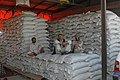 Workers sit on bags of soybeans ready for processing at the Bastan Seed Company in Parwan, Afghanistan, Aug. 12, 2010 100821-A-SQ512-003.jpg