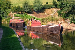 Narrowboat - Historic working narrow boats on the Macclesfield Canal in Cheshire, England. The leading boat, Forget Me Not, is hauling the un-powered butty Lilith. This became a familiar operating pattern once motors began to replace horses.