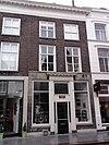 foto van Pand met twee verdiepingen onder met blauwe hollandse pannen gedekt zadeldak tegen topgevel met vlechtingen en met schild boven de in schoon metselwerk opgetrokken 19e-eeuwse en door een geprofile