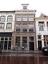 foto van Huis met lijstgevel met rijke kroonlijst, bestaande uit parel- en eierlijsten, guirlandes en osseschedels, klossen met druppen