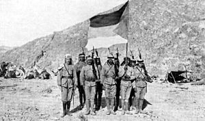 History of Saudi Arabia - Soldiers in the Arab Army during the Arab Revolt of 1916–1918, carrying the Flag of the Arab Revolt and pictured in the Arabian Desert.