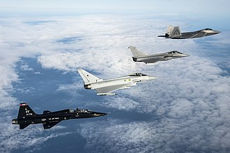 Military aircraft - A U.S. Air Force T-38 Talon, British Royal Air Force Eurofighter Typhoon, French Air Force Dassault Rafale and U.S. Air Force F-22 Raptor fly in formation.