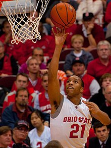 an African American wearing Ohio State jersey #21 attempts a one handed shot from the side of the basket.