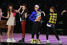Four women wearing colourful, mismatched casual clothing and trendy sneakers
