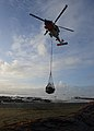 A Coast Guard MH-60 Jayhawk helicopter crew lifting a net full of beach debris.jpg
