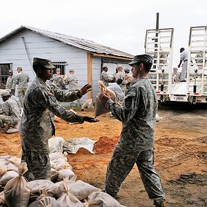 State defense force - A Georgia State Defense Force Volunteer passes a sandbag to a Georgia Army National Guard Soldier during a flood preparation mission.