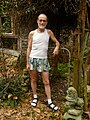 A Man Is Wearing a Tank Top and Men's Skirt with Socks and Sandals..jpg