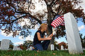 A U.S. Coast Guard family member places a U.S. flag at a tombstone during a Flags Across America event Nov. 2, 2013, at Arlington National Cemetery in Arlington, Va 131102-G-ZX620-244.jpg