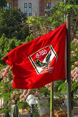 A flag with the crest of Egyptian association football club Al Ahly، on a red background، can be seen.