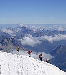 Mountaineers descending steep snow ridge above Chamonix