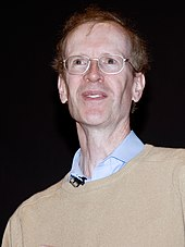 A white man wearing glasses and a shirt looking upward