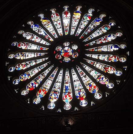 Angers Cathedral South Rose Window of Christ (centre) with elders (bottom half) and Zodiac (top half). Mediaeval stained glass by Andre Robin after the fire of 1451 Angers Cathedral South Rose Window of Christ with Zodiac.jpg