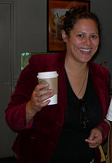 A smiling woman wearing a red jacket leaning on a bench holding a cup. Her black hair is pulled back.