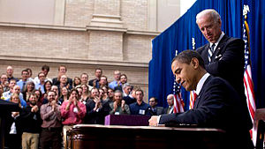 Presidency of Barack Obama - President Obama signs the ARRA into law on February 17, 2009 in Denver, Colorado. Vice President Joe Biden stands behind him.