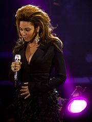 A woman is standing with a microphone in her right hand and touches her abdomen with her left hand. She is wearing a black dress and earrings while being illuminated by a purple light in the background of the stage.