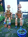 Bill and Ben - whimsical flower pot men on a stone bench in Shere's Lower Street, Surrey, 2008.jpg