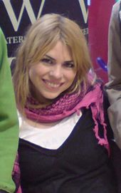 A woman in early 20s with blonde hair and brown eyes, smiling, wearing a white T-shirt, a black tank top and a pink scarf.