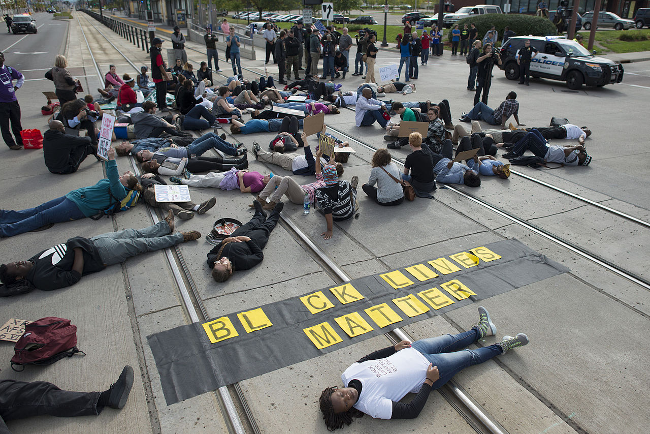 "Protesters lying down over rail tracks with a ""Black Lives Matter"" banner"