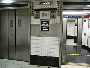 "Elevator - A set of lifts in the lower level of Borough station on the London Underground Northern line. The ""up"" and ""down"" arrows indicate each lift's position and direction of travel.  Notice how the next lift is indicated with a right and left arrow by the words ""Next Lift"" at the top."