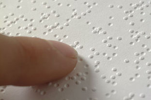 finger tip touching page with raised dots