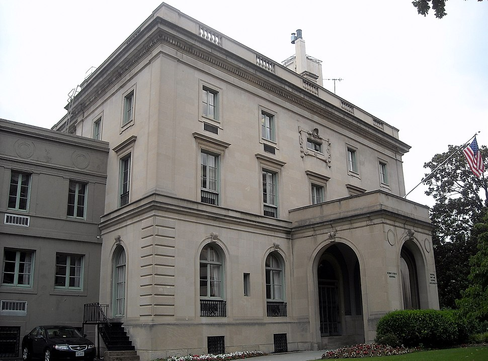 A three-story gray mansion, with a covered front entrance