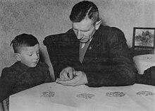Photo en noir et blanc montrant un enfant et un homme assis à une table
