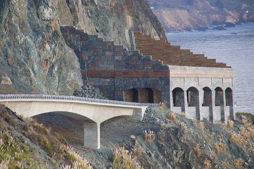 A highway bridge leads to a rock shelter protecting the roadway from rocks falling off the cliff above.