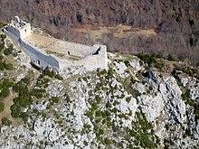 Photographie aérienne contemporaine de ruines d'un château bâti sur une éminence.