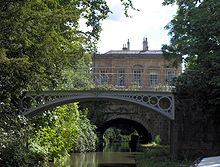 A iron bridge spanning water. In the background is a yellow stone building. On the left tress reach out over the water.