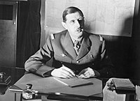 Commander of Free French Forces General Charles de Gaulle seated at his desk in London during the Second World War. D1973.jpg