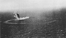 Une large colonne de fumée s'élevant d'un navire vue depuis le ciel