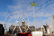 An image of the funfair in Dam square showing a Ferris wheel on the left, behind it spinning-arm ride called Speed; and a Matterhorn on the right with its spinning cars at maximum extension.