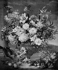 Stor blomsterbuket i en vase. I forgrunden frugter, til venstre en papegøje